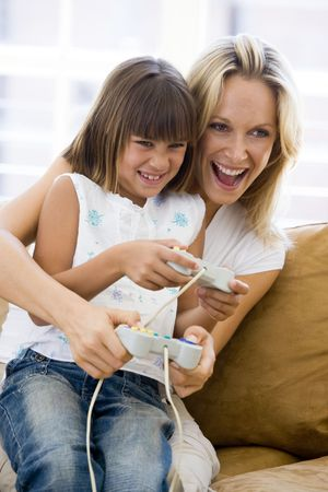 Woman and young girl in living room with video game controllers smiling Stock Photo - 3602886