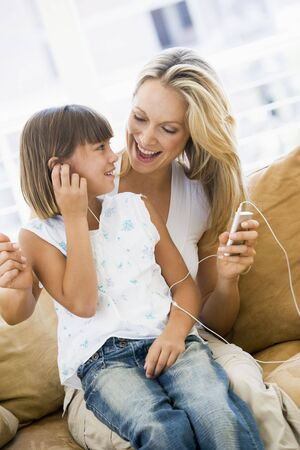 woman listening to music: Woman and young girl in living room with MP3 player smiling