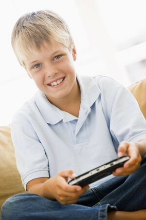 Young boy in living room with handheld video game smiling Stock Photo - 3601495