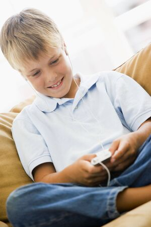 Young boy in living room with MP3 player smiling Stock Photo - 3602719