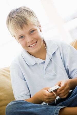 Young boy in living room with MP3 player smiling Stock Photo - 3601390