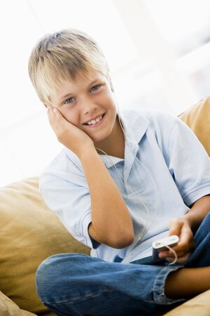 Young boy in living room with MP3 player smiling Stock Photo - 3602751