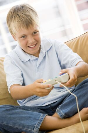 videogame: Young boy in living room with video game controller smiling Stock Photo