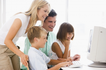 Family in home office using computer smiling photo