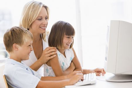 mom and child: Woman and two young children in home office with computer smiling