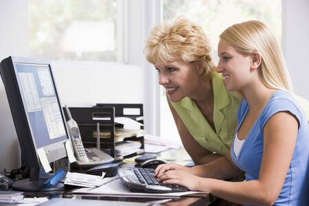 Woman and girl in home office with computer smiling photo