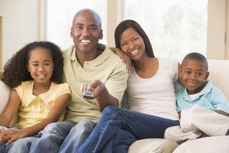 personas mirando: Familia sentado en sala de estar con control remoto sonriente