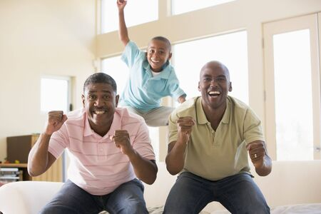 Two men and young boy in living room cheering and smiling photo