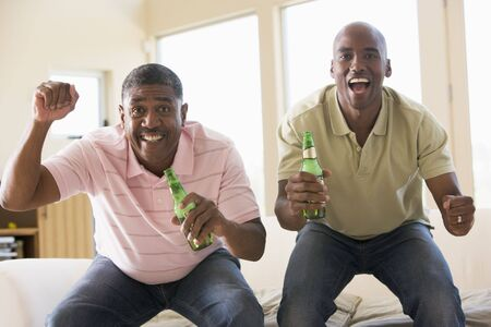 people celebrating: Two men in living room with beer bottles cheering and smiling