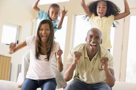 Family in living room cheering and smiling photo