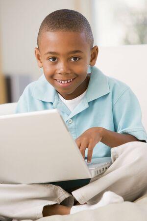 garcon africain: Jeune gar�on dans le salon avec un ordinateur portable en souriant