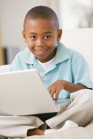 african american boy: Young boy in living room with laptop smiling
