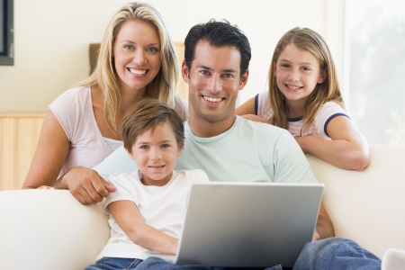 Family in living room with laptop smiling Stock Photo - 3601364
