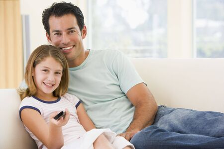 Man and young girl in living room with remote control smiling photo