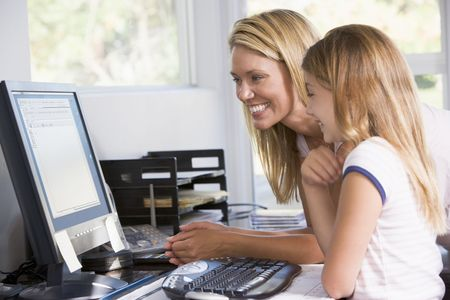 Woman and young girl in home office with computer smiling photo