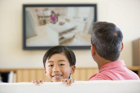 viewing: Uomo e giovane ragazzo nel salotto con schermo piatto televisione sorridente