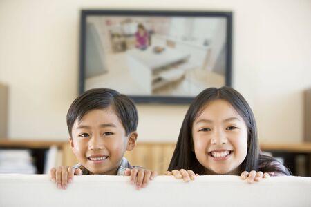mujer viendo tv: Dos ni�os de corta edad en la sala de estar con televisi�n de pantalla plana sonriente  Foto de archivo