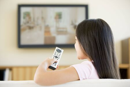 Young girl in living room with flat screen television and remote control photo