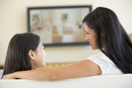 mums: Woman and young girl in living room with flat screen television smiling Stock Photo
