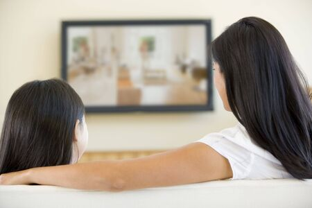woman watching tv: Woman and young girl in living room with flat screen television