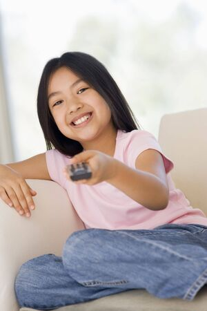 flatscreen: Young girl in living room with remote control smiling Stock Photo