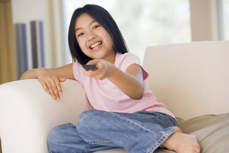 Young girl in living room with remote control smiling Stock Photo - 3600792