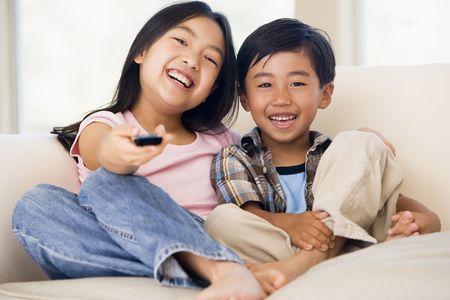 viewing: Due youngchildren in soggiorno con telecomando sorridente Archivio Fotografico