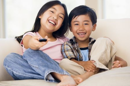 kid pointing: Two youngchildren in living room with remote control smiling
