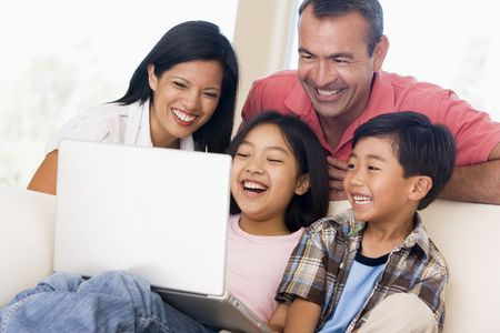 Family in living room with laptop smiling Stock Photo - 3602703