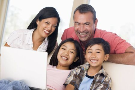 Family in living room with laptop smiling photo