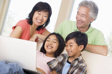 asian office lady: Couple with two young children in living room with laptop smiling Stock Photo