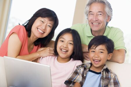 Couple with two young children in living room with laptop smiling photo