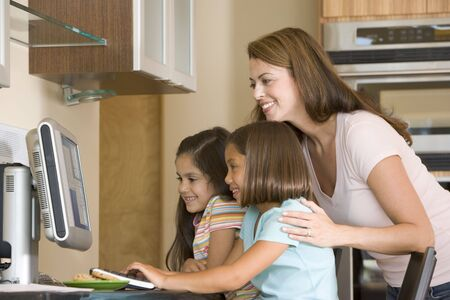 Woman and two young girls in kitchen with computer smiling Stock Photo - 3602714