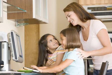 Woman and two young girls in kitchen with computer smiling photo