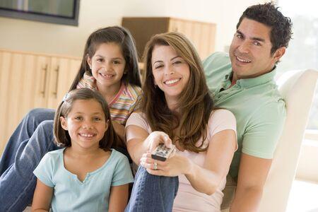 personas viendo television: Familia en la sala de estar con control remoto sonriente