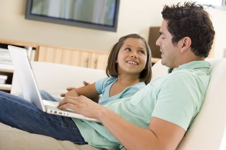 Man with young girl in living room with laptop smiling photo