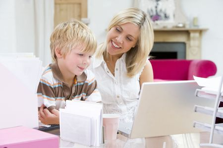 Woman and young boy in home office with laptop smiling photo