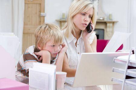 madre trabajando: Mujer utilizando tel�fono en la oficina con ordenador port�til, mientras que espera ni�o