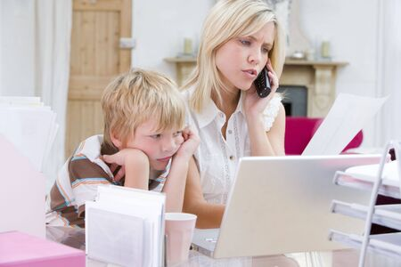 Woman using telephone in home office with laptop while young boy waits photo