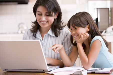 working: Woman and young girl in kitchen with laptop and paperwork smiling