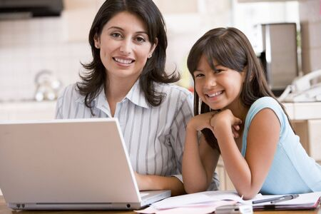 Woman and young girl in kitchen with laptop and paperwork smiling Stock Photo - 3602753