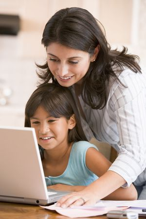 latin girls: Woman and young girl in kitchen with laptop and paperwork smiling