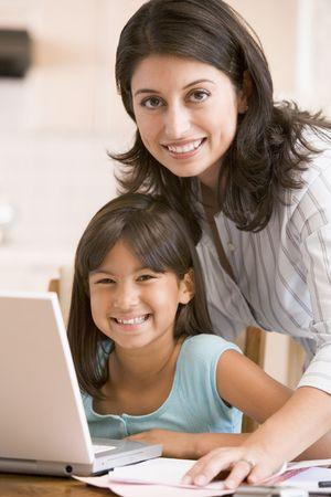 mamans: Femme et jeune fille dans la cuisine avec un ordinateur portable paperasse et sourire Banque d'images