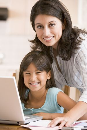 Woman and young girl in kitchen with laptop and paperwork smiling photo