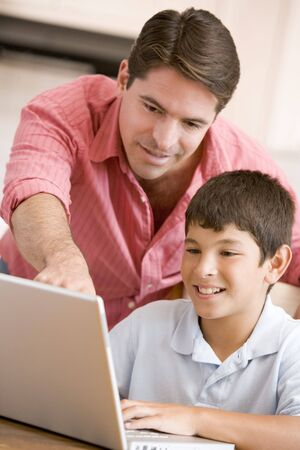 Man helping young boy in kitchen with laptop smiling photo
