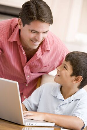 Man helping young boy in kitchen with laptop smiling Stock Photo - 3602976