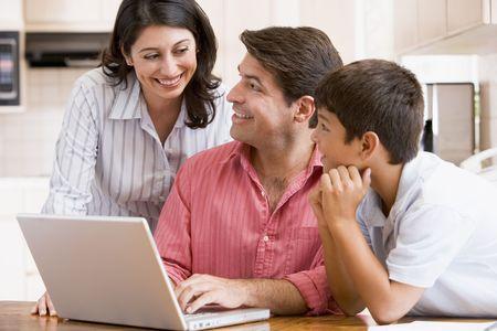 Familia en la cocina con el portátil sonriente