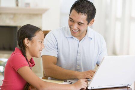 deberes: Hombre y ni�a con ordenador port�til en sala sonriendo