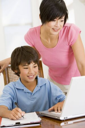 Woman helping young boy with laptop do homework in dining room smiling Stock Photo - 3602892