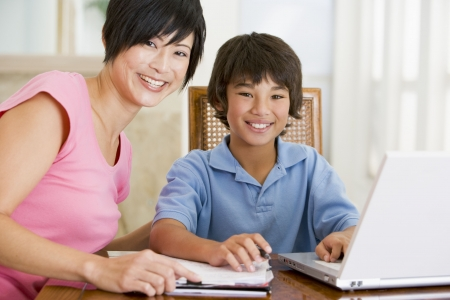 Woman helping young boy with laptop do homework in dining room smiling photo